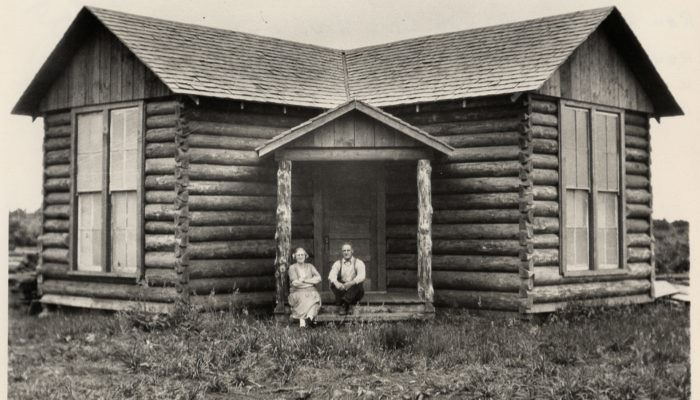 Old Photo of Two People Sitting on the Steps of the Little Log Church